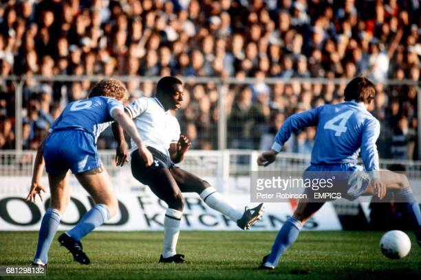 Tottenham Hotspur's Garth Crooks lays the ball square as he is confronted by Manchester City's Tommy Caton and Nicky Reid