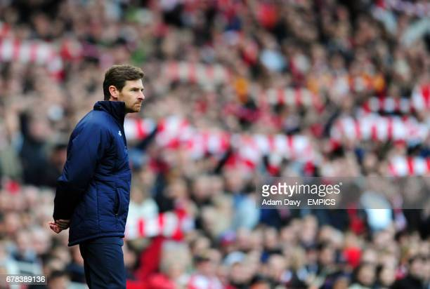 Tottenham Hotspur's Manager Andre Villas Boas stands as Arsenal fans waves scarves in the background