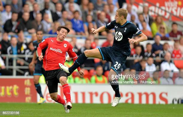 Tottenham Hotspur's Michael Dawson catches the thigh of Cardiff City's Kim BoYung as they battle for the ball during the Barclays Premier League...