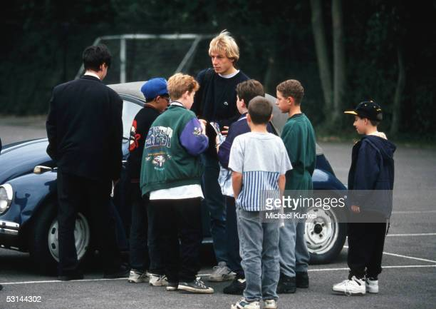 Tottenham Hotspurs player Juergen Klinsmann is surrounded by fans as he arrives with his car at the parking ground in front of the Tottenham training...