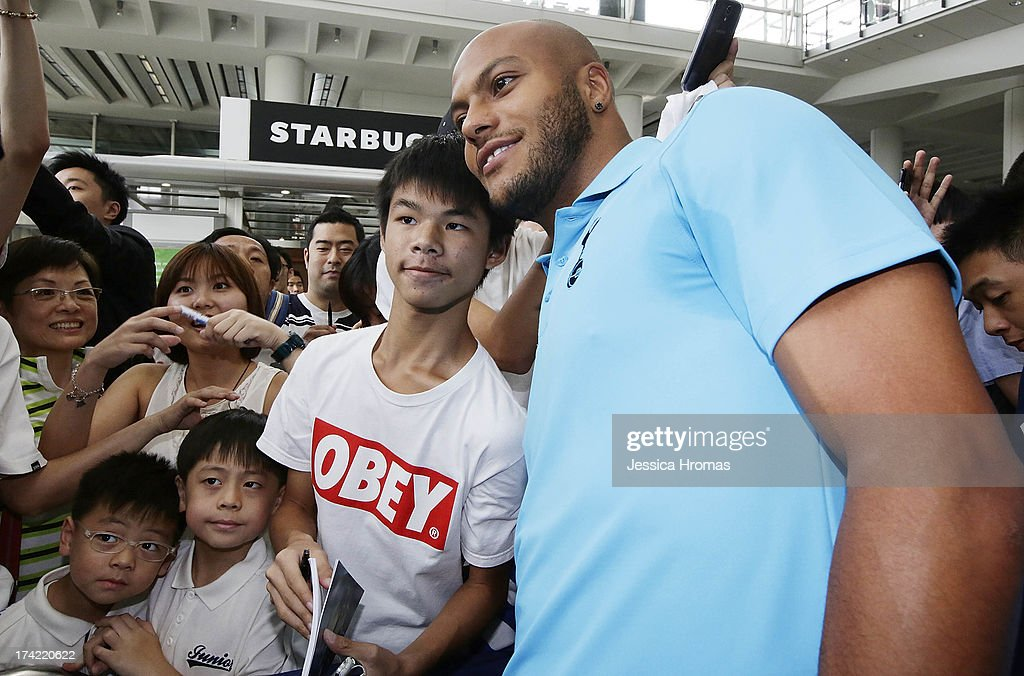 Tottenham Hotspur's player <a gi-track='captionPersonalityLinkClicked' href=/galleries/search?phrase=Younes+Kaboul&family=editorial&specificpeople=685970 ng-click='$event.stopPropagation()'>Younes Kaboul</a> poses for a photo fwith a fans at Hong Kong Airport, the Tottenham Hotspur team arrive to compete in the Barclays Asia Trophy, on July 22, 2013 in Hong Kong.