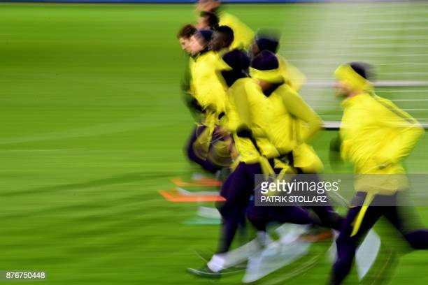 Tottenham Hotspur's players warm up during a training session on the eve of the Champion's League Group H football match Borussia Dortmund against...