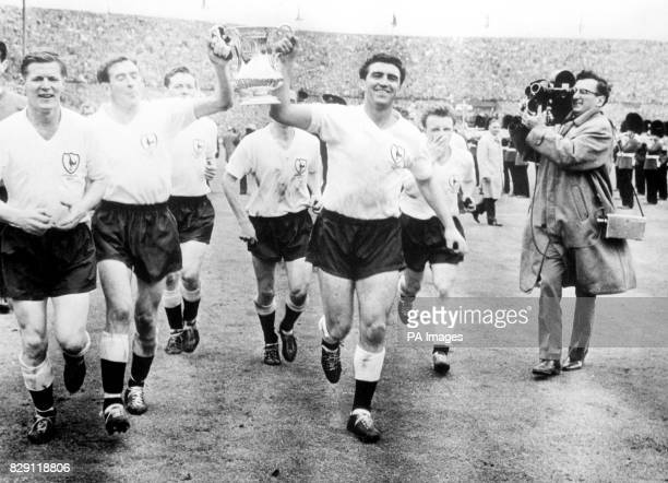 Tottenham Hotspurs righthalf captain Danny Blanchflower and centreforward Bobby Smith gaily trot the FA Cup before the 100000 crowd at the Empire...