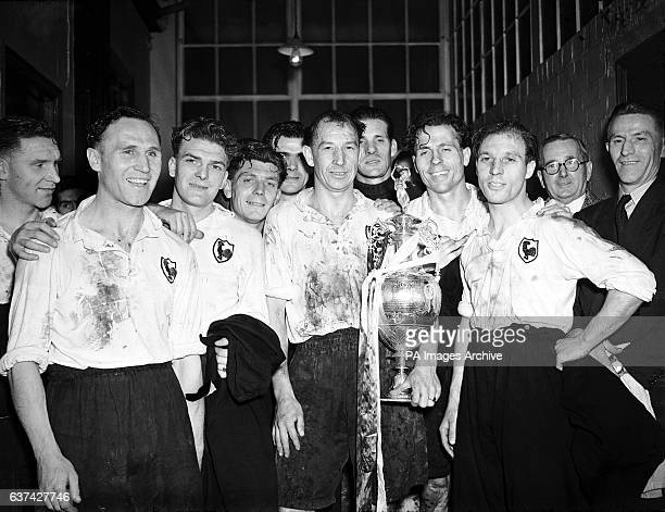Tottenham Hotspur's Ron Burgess holds on to the League Championship trophy as his teammates bask in the satisfaction of having won the League in...