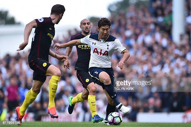 Tottenham Hotspur's South Korean striker Son HeungMin vies with Manchester City's English defender John Stones and Manchester City's Argentinian...