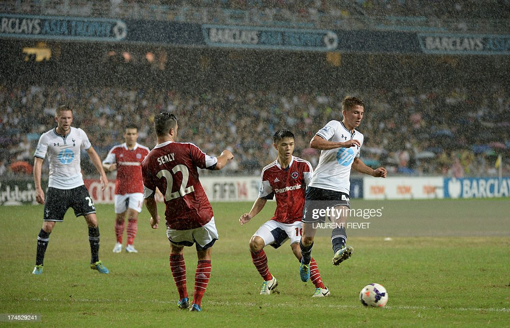 Tottenham Hotspur's Tom Carroll competes for the ball against South China's Chan Siu Kwan and Jonathan Sealy during their Barclays Asia trophy third...