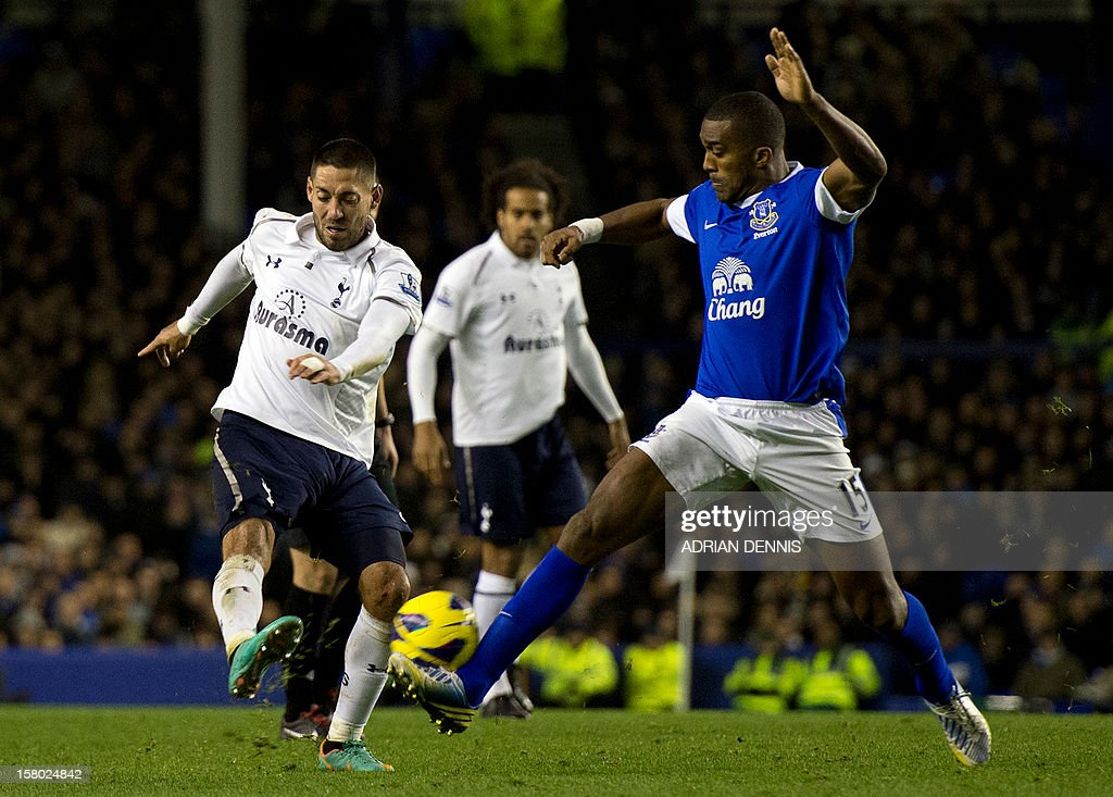 """Tottenham Hotspur's US striker Clint Dempsey (L) shoots to score the opening goal past Everton's French defender Sylvain Distin (R) during the English Premier League football match between Everton and Tottenham Hotspur at Goodison Park in Liverpool, north-west England on December 9, 2012. USE. No use with unauthorized audio, video, data, fixture lists, club/league logos or """"live"""" services. Online in-match use limited to 45 images, no video emulation. No use in betting, games or single club/league/player publications"""