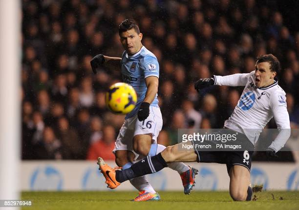 Tottenham Hotspur's Vlad Chiriches slides in as Manchester City's Sergio Aguero has a shot on goal