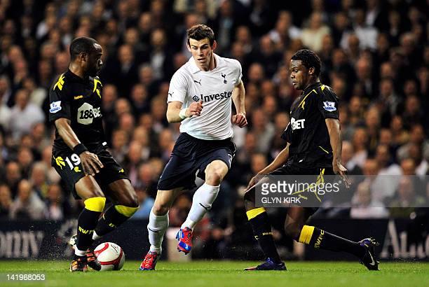 Tottenham Hotspur's Welsh defender Gareth Bale vies with Bolton Wanderers' English midfielder Nigel ReoCoker and Belgian defender Dedryck Boyota...