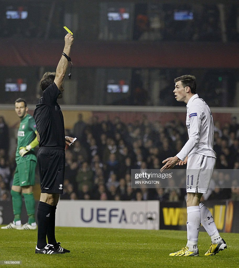 Tottenham Hotspur's Welsh footballer Gareth Bale (R) is given the yellow card by the referee during a UEFA Europa League Round of 16 football match between Tottenham Hotspur and Inter Milan at White Hart Lane in east London, on March 7, 2013.