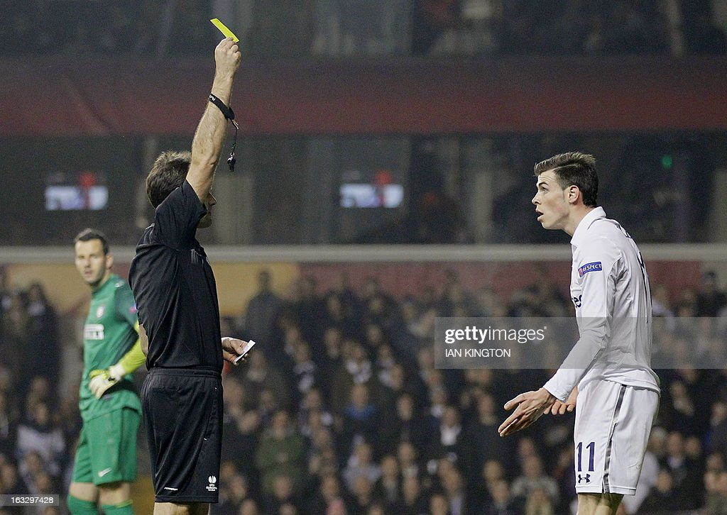 Tottenham Hotspur's Welsh footballer Gareth Bale (R) is given the yellow card for diving by the referee during a UEFA Europa League Round of 16 football match between Tottenham Hotspur and Inter Milan at White Hart Lane in east London, on March 7, 2013.