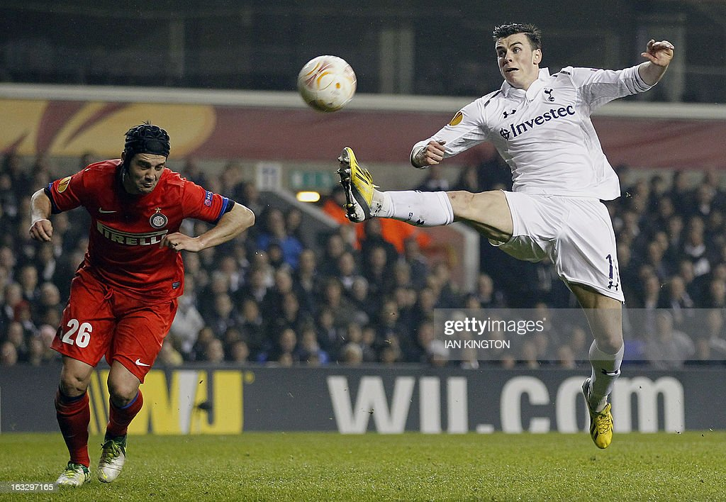 Tottenham Hotspur's Welsh footballer Gareth Bale (R) stretches for the ball against Inter Milan's Romanian defender Christian Chivu during a UEFA Europa League Round of 16 football match between Tottenham Hotspur and Inter Milan at White Hart Lane in east London, on March 7, 2013.