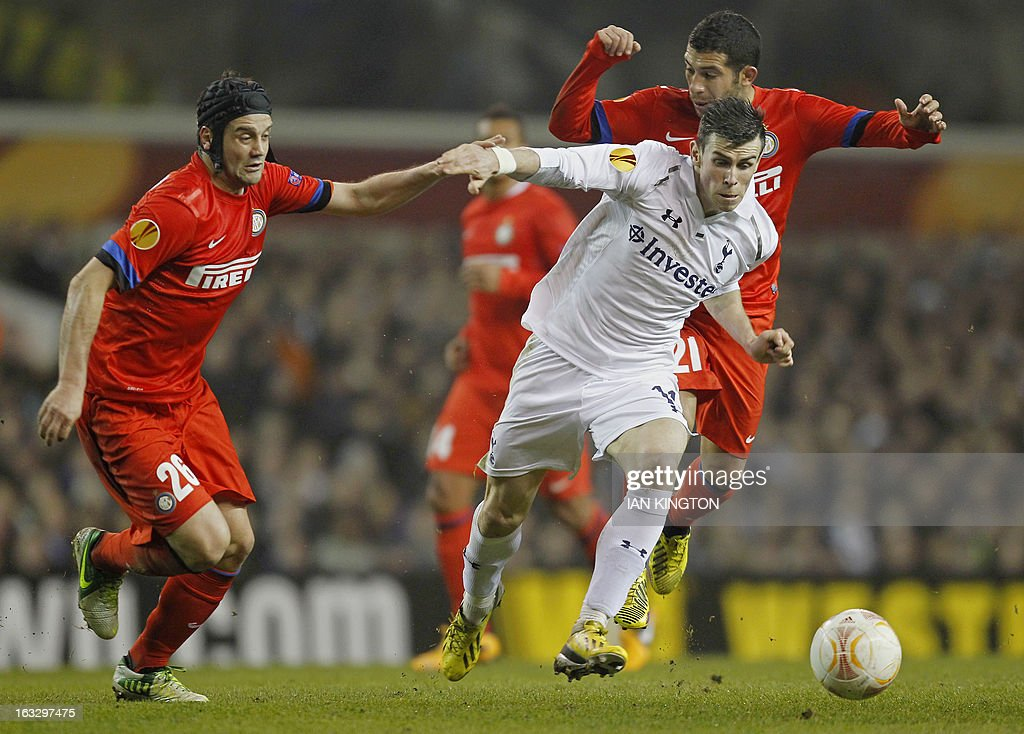 Tottenham Hotspur's Welsh footballer Gareth Bale (Foreground) vies for the ball with Inter Milan's Romanian defender Christian Chivu (L) and Inter Milan's Uruguayan midfielder Walter Gargano (R) during a UEFA Europa League Round of 16 football match between Tottenham Hotspur and Inter Milan at White Hart Lane in east London, on March 7, 2013.