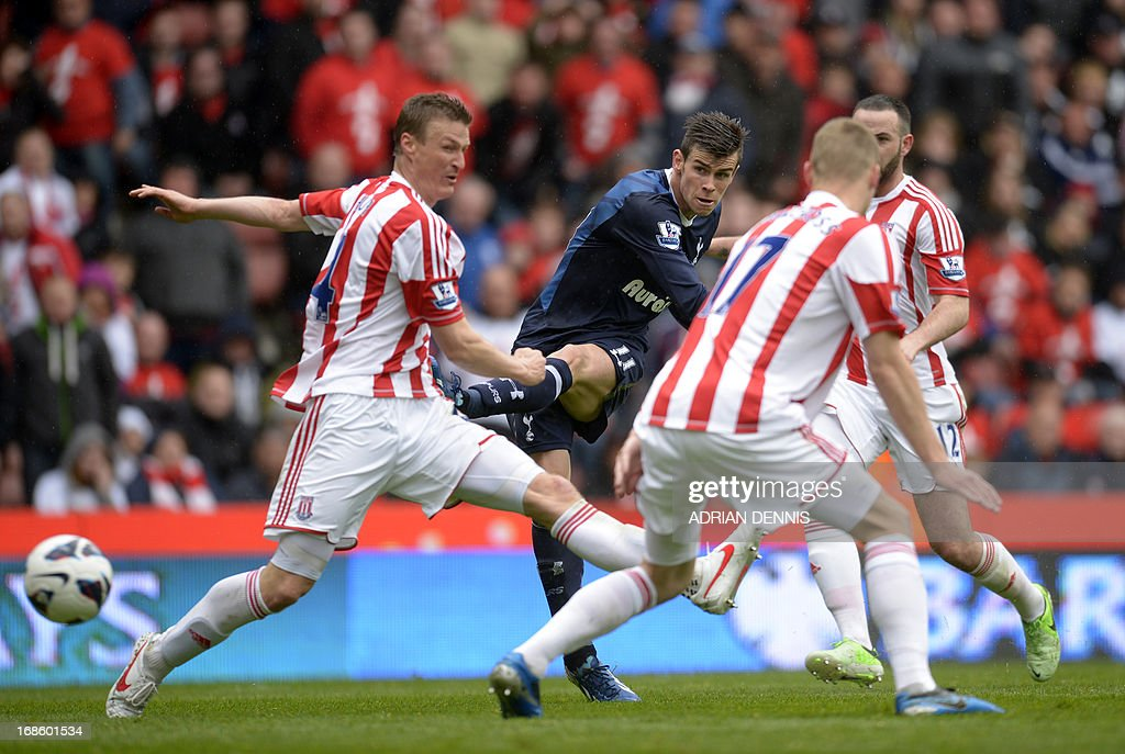 """Tottenham Hotspur's Welsh midfielder Gareth Bale (2L) takes a shot at goal past Stoke City's German defender Robert Huth (L) during the English Premier League football match between Stoke City and Tottenham Hotspur at the Britannia Stadium in Stoke on Trent, central England, on May 12, 2013. USE. No use with unauthorized audio, video, data, fixture lists, club/league logos or """"live"""" services. Online in-match use limited to 45 images, no video emulation. No use in betting, games or single club/league/player publications."""