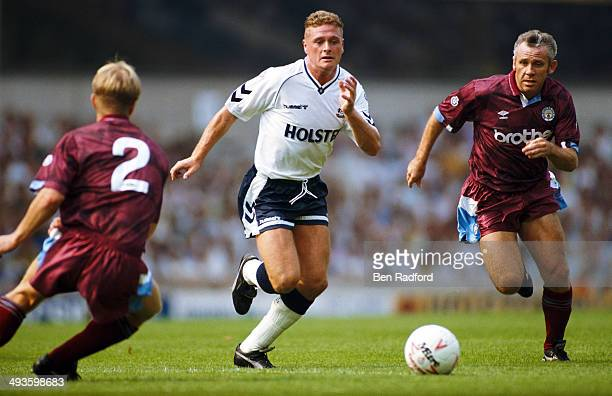 Tottenham player Paul Gascoigne races past Peter Reid during a Division One match between Tottenham Hotspur and Manchester City at White Hart Lane on...