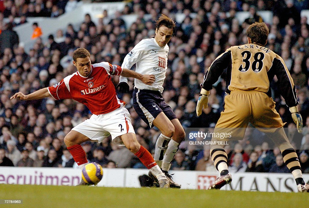 Tottenham Hotspur player Dimitar Berbatov (C) is tackled by Charlton defender Luke Young (L) as Charlton lose 5-1 during the English Premiership match at White Hart Lane in north London, 09 December 2006. AFP PHOTO / GLENN CAMPBELL Mobile and website use of domestic English football pictures subject to subscription of a license with Football Association Premier League (FAPL) tel : +44 207 298 1656. For newspapers where the football content of the printed and electronic versions are identical, no licence is necessary.