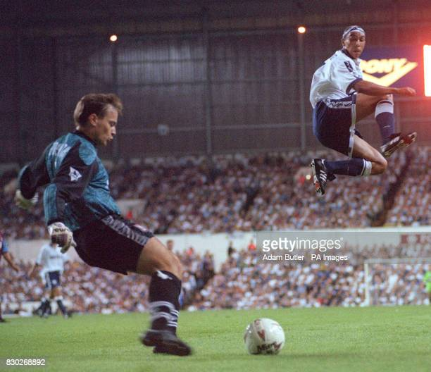 Tottenham's new signing Chris Armstrong leaps out of the way as Aston Villa's goalkeeper Mark Bosnich clears the ball during the Premier League match...