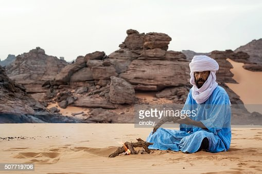 Touareg makes a campfire in the Akakus Mountains, Libya desert