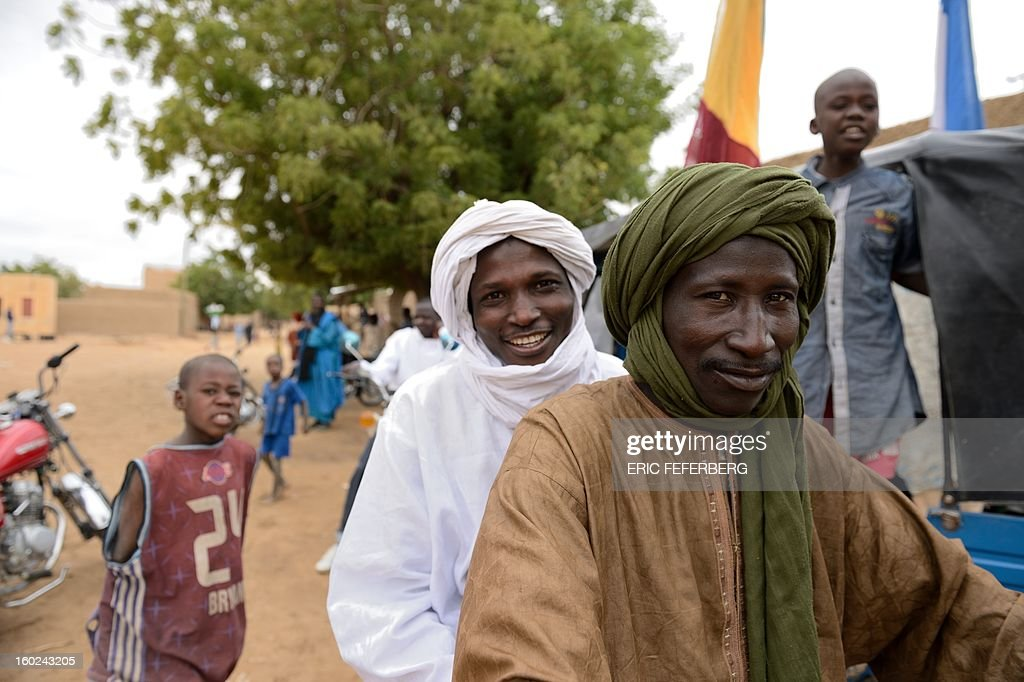 Touareg people celebrate in Niafounke as Malian and French soldiers entered the historic city of Timbuktu, occupied for 10 months by Islamists who imposed a harsh form of sharia, on January 28, 2013. French-led forces today seized Mali's fabled desert city of Timbuktu in a lightning advance north as fleeing Islamists torched a building housing priceless ancient manuscripts. Residents of the ancient city on the edge of the Sahara desert erupted in joy as the French-led troops entered the town, jubilantly waving French and Malian flags after months of suffering under the Islamists' brutal rule.