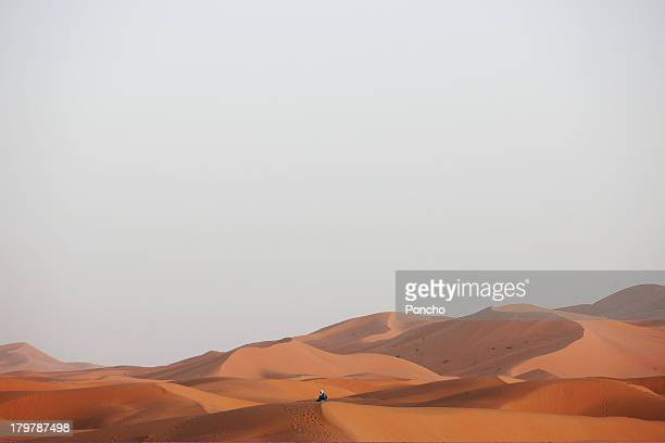 Touareg sitting at a sand dune
