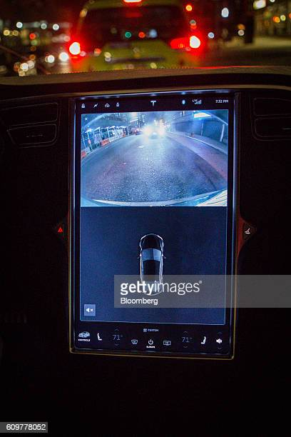 A touchscreen control panel with the Tesla Motors Inc 80 software update displays images from the rear view mirror camera inside a Model S P90D...