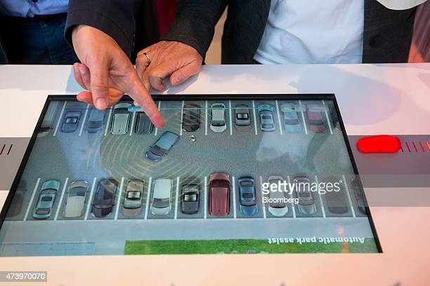 A touchscreen panel shows a demonstration of an automated car parking assistance app at Robert Bosch GmbH driverless technology press event in...