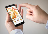 Close up of man using 3d generated mobile smart phone with  order food online website on the screen. Screen graphics are made up.