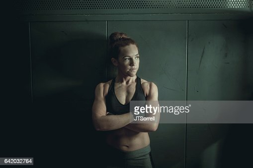 Tough and Athletic Woman Leaning up Against a Wall
