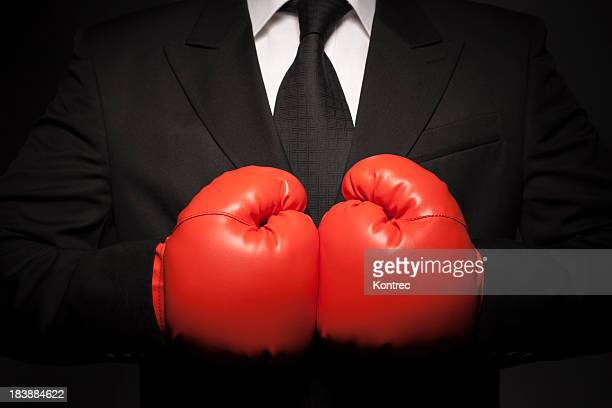 Tough businessman in black suit and red boxing gloves