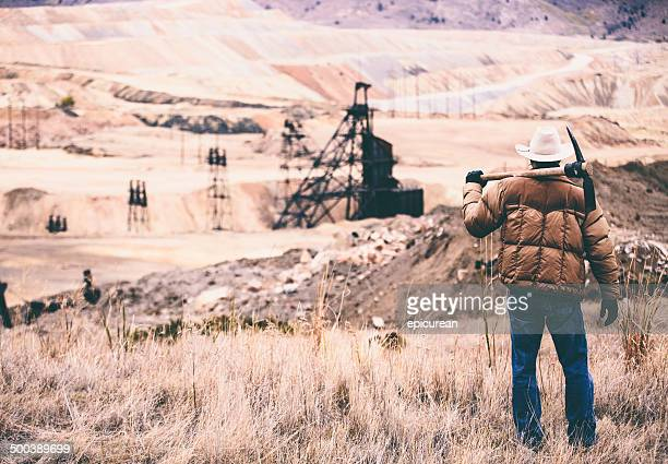 Tough man stands in rock quarry with old oil drill