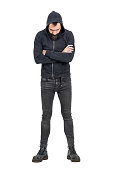Tough punker in black hooded sweatshirt with crossed arms looking down. Full body length portrait isolated over white studio background