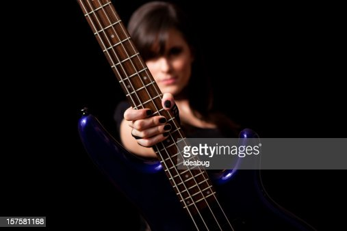 Tough Rocker Girl Holding Bass Guitar on Black Background