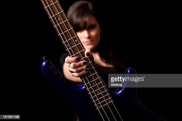 Tough Rocker Girl Holding Bass Guitar on Black Background