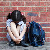 School girl. Tough times. Concept for bullying or challenges with growing up. A young girl wearing her school uniform sits with her head down. She is against a brick wall and her school bag sits along