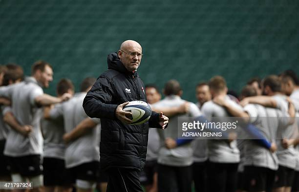 Toulon coach Bernard Laporte looks on as his players huddle on the field during a training session at Twickenham Stadium south west of London on May...