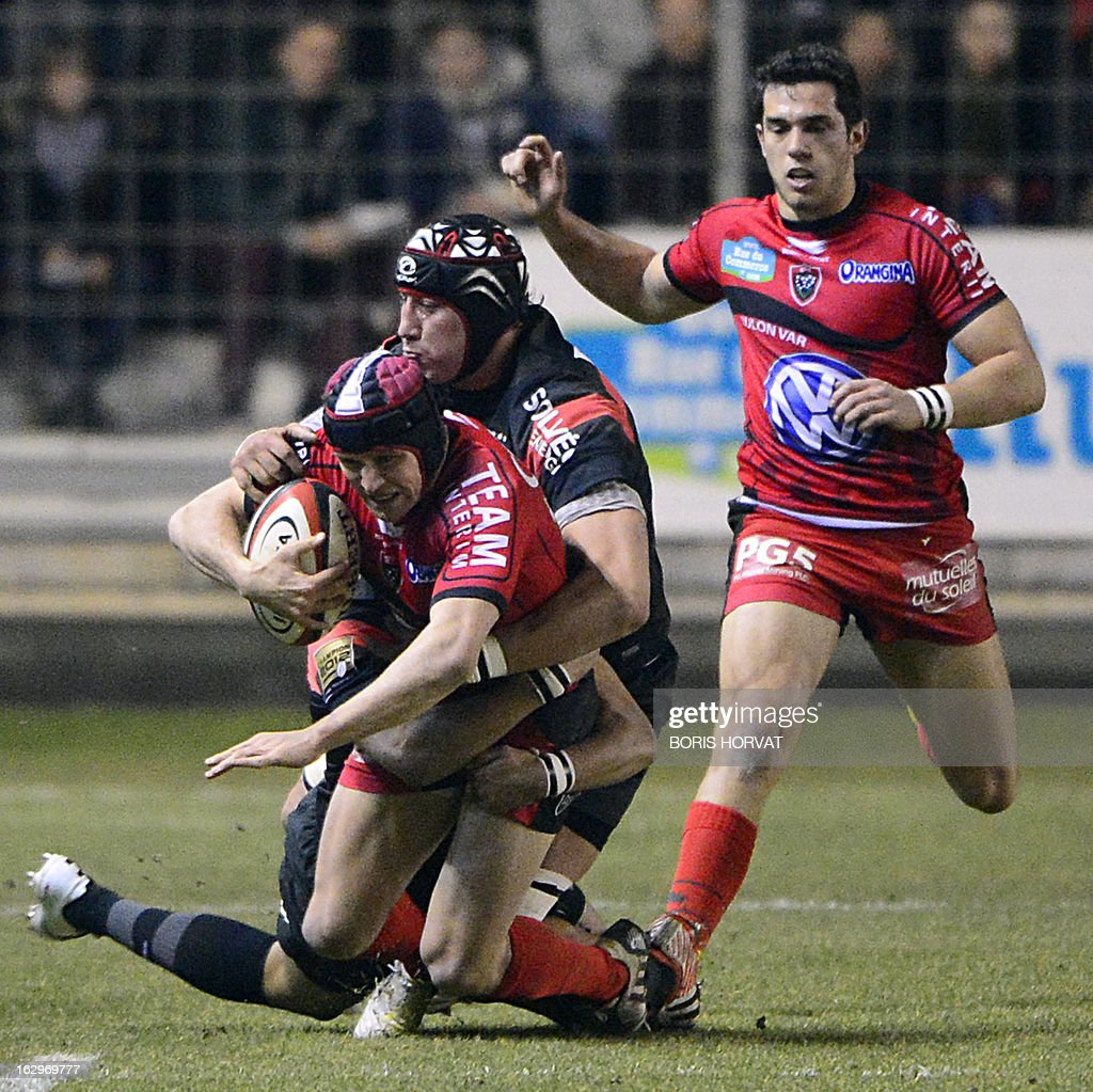 Toulon's Australian fly-half Matt Giteau (L) is tackled by Toulouse's Argentinian lock Patricio Albacete (2ndL) during the French Top 14 rugby Union match RC Toulon versus Toulouse on March 2, 2013, at the Mayol stadium in the French southern city of Toulon.