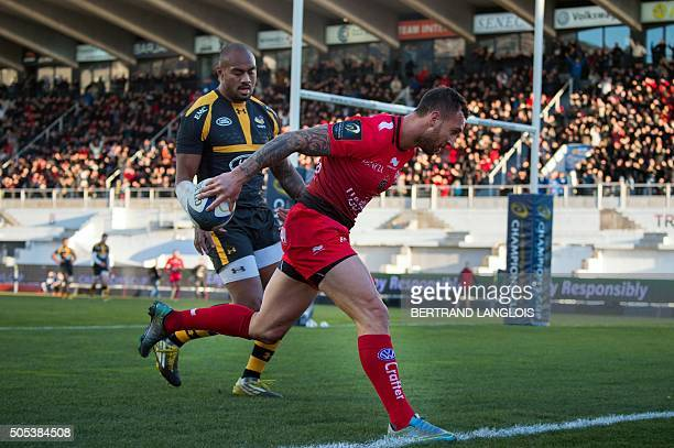RC Toulon's Australian flyhalf Quade Cooper scores a try despite Wasps' FijianSamoan wing from Sailosi Tagicakibau during the European Champions Cup...