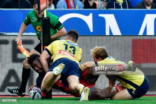 Toulon's flyhalf Josua Tuisova scores a try despite Clermont's centre Damien Penaud during the French Top 14 rugby union final match Clermont vs...