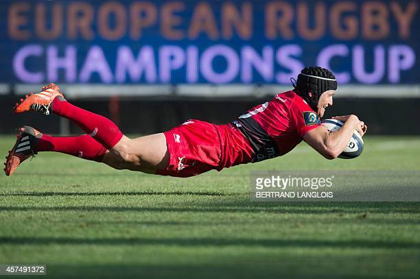 Toulon's flyhalf Matt Giteau dives to score a try during the European Rugby Champions Cup match between Toulon and Llanelli Scarlets at the Mayol...