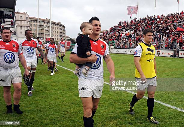 Toulon's French centre Geoffroy Messina reacts holding a baby in his arms after winning the French Top 14 rugby union match Toulon vs Toulouse at the...