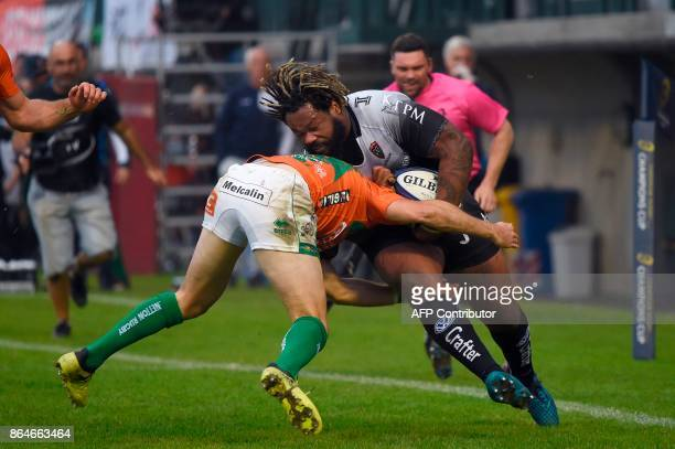 Toulon's French centre Mathieu Bastareaud is tackled by Benetton Treviso's Irish fullback Ian McKinley during the European Rugby Champions Cup rugby...