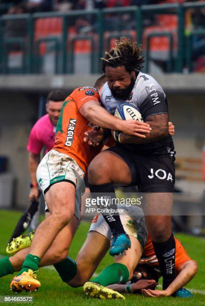 Toulon's French centre Mathieu Bastareaud is tackled by Benetton Treviso's Italian centre Alberto Sgarbi and Benetton Treviso's Irish fullback Ian...