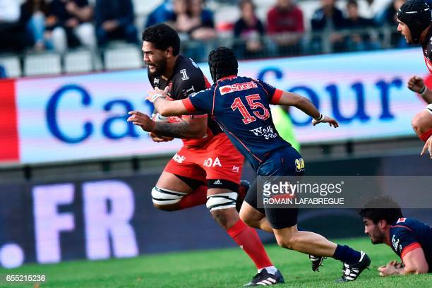 Toulons French lock Romain Taofifenua fends off the tackle of Grenobles French fullback Fabien Gengenbacher on his way to score a try during the...