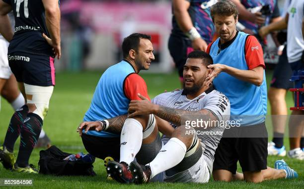 RC Toulon's French lock Romain Taofifenua is helped by medical staff during the French Top 14 rugby union match between Stade Francais and Toulon at...