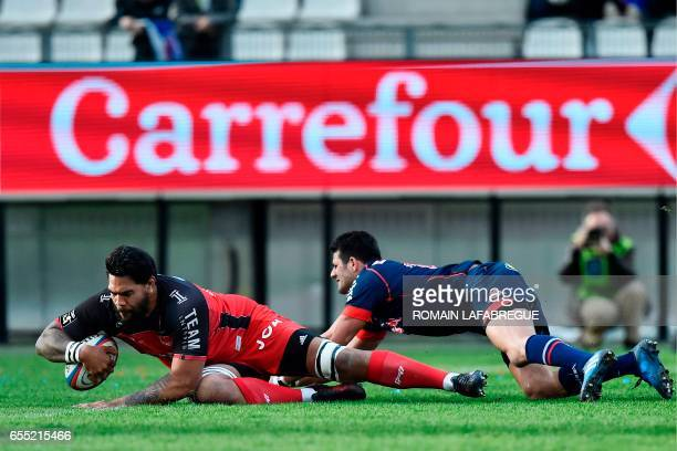 Toulons French lock Romain Taofifenua scores a try despite Grenobles French fullback Fabien Gengenbacher during the French Top 14 rugby union match...