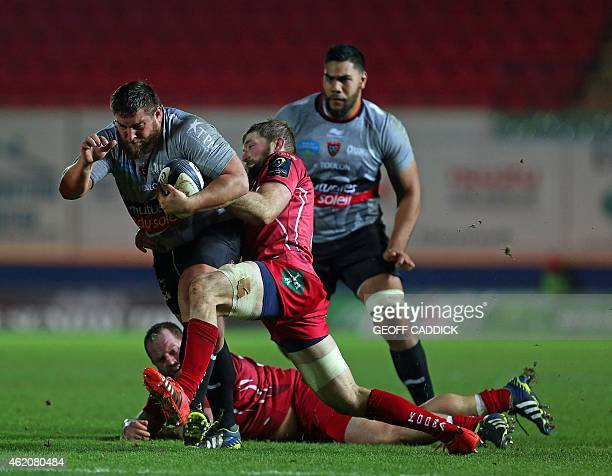 Toulon's French prop Xavier Chiocci is tackled by Scarlet's Scottish flanker John Barclay during the European Rugby Champions Cup rugby union match...