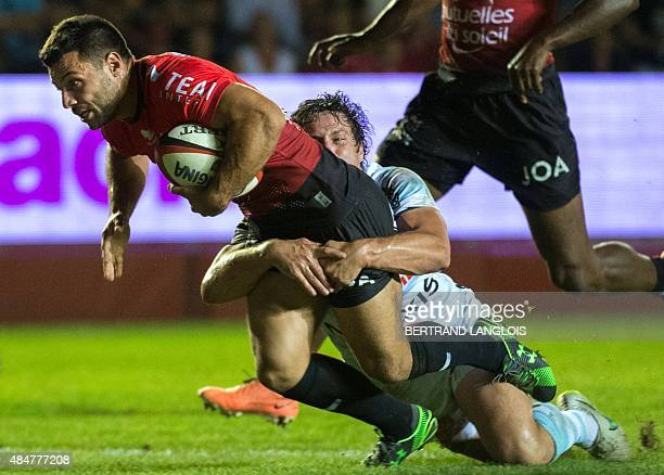RC Toulon's French scrumhalf Jonathan Pelissie dives to score a try despite the tackle from Racing Metro French centre Henry Chavancy during the...