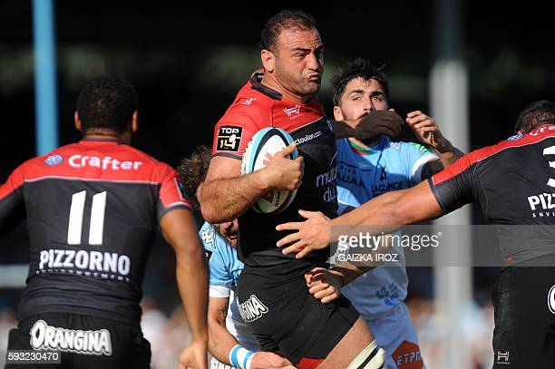 Toulon's Georgian flanker Mamuka Gorgodze is tackled by Bayonne's French center Julien Jane during the French Top 14 rugby union match between...