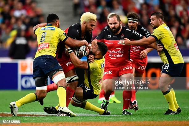 Toulon's lock Romain Taofifenua is tackled by Clermont's number eight Fritz Lee during the French Top 14 rugby union final match Clermont vs Toulon...