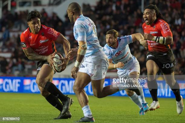 RC Toulon's New Zealand centre Malakai Fekitoa runs with the ball from Racing92's New Zealand winger Joe Rokocoko and Racing92's winger Marc Andreu...